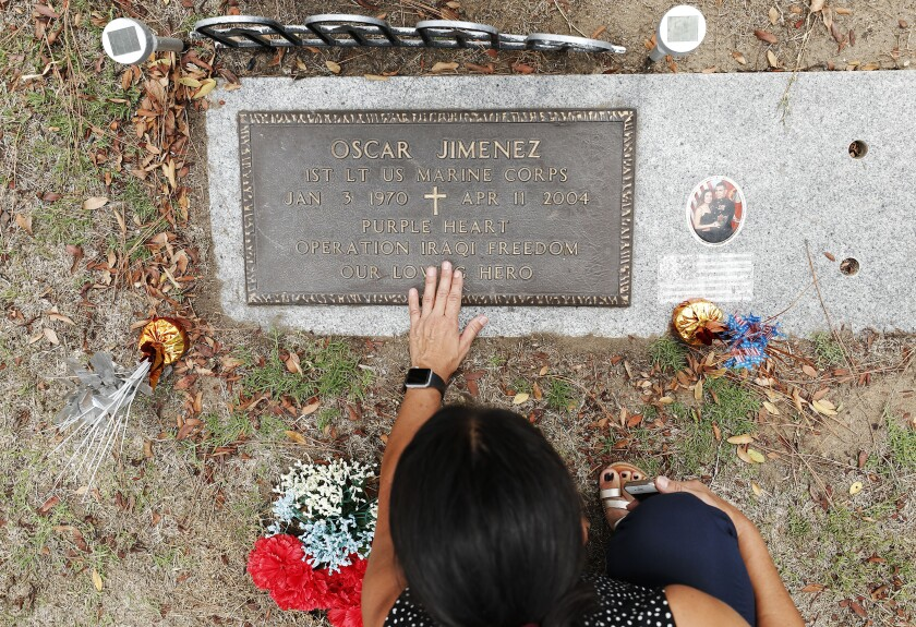 Sonia Jimenez visits the grave of her brother Oscar Jimenez at Greenwood Memorial Park in San Diego.