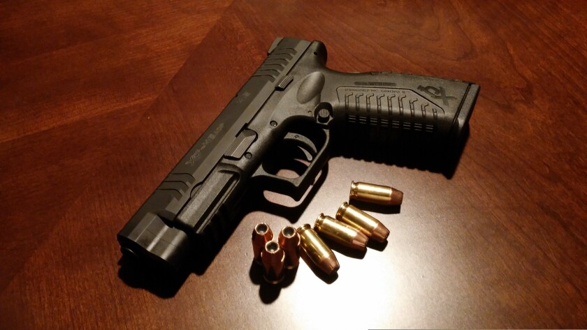 A handgun with bullets on a table.