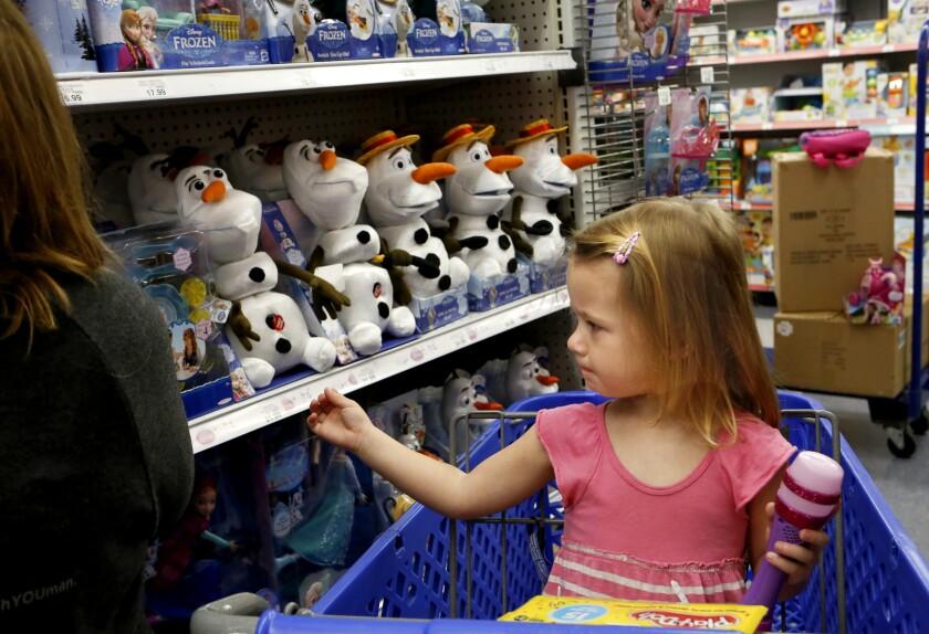 Siena David, 3, reaches toward the shelf of merchandise from Disney's movie Frozen