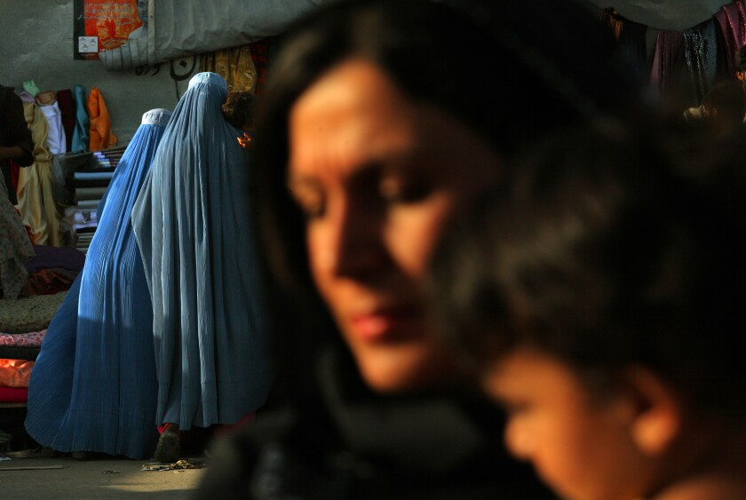 Two women in burqas walk outdoors