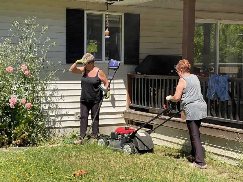 A woman sizes up a weed as another mows a lawn