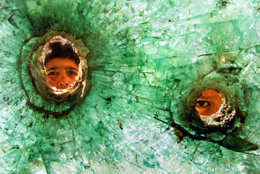 Two boys faces seen through bullet holes in shattered glass