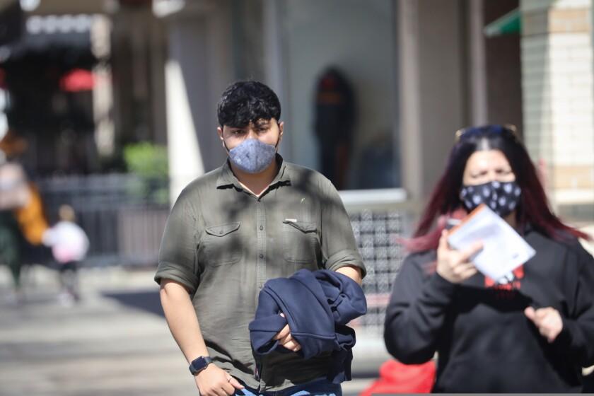 People wearing masks walk around Downtown Santa Cruz on Feb. 23, 2021.