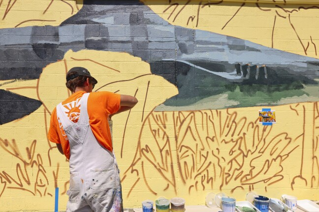 """David Rice of Portland, Oregon, works on his """"Shark Conservation"""" mural Monday off Front Street."""