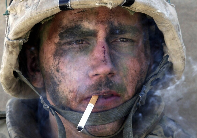 A closeup of a Marine smoking a cigarette, his face covered in dirt