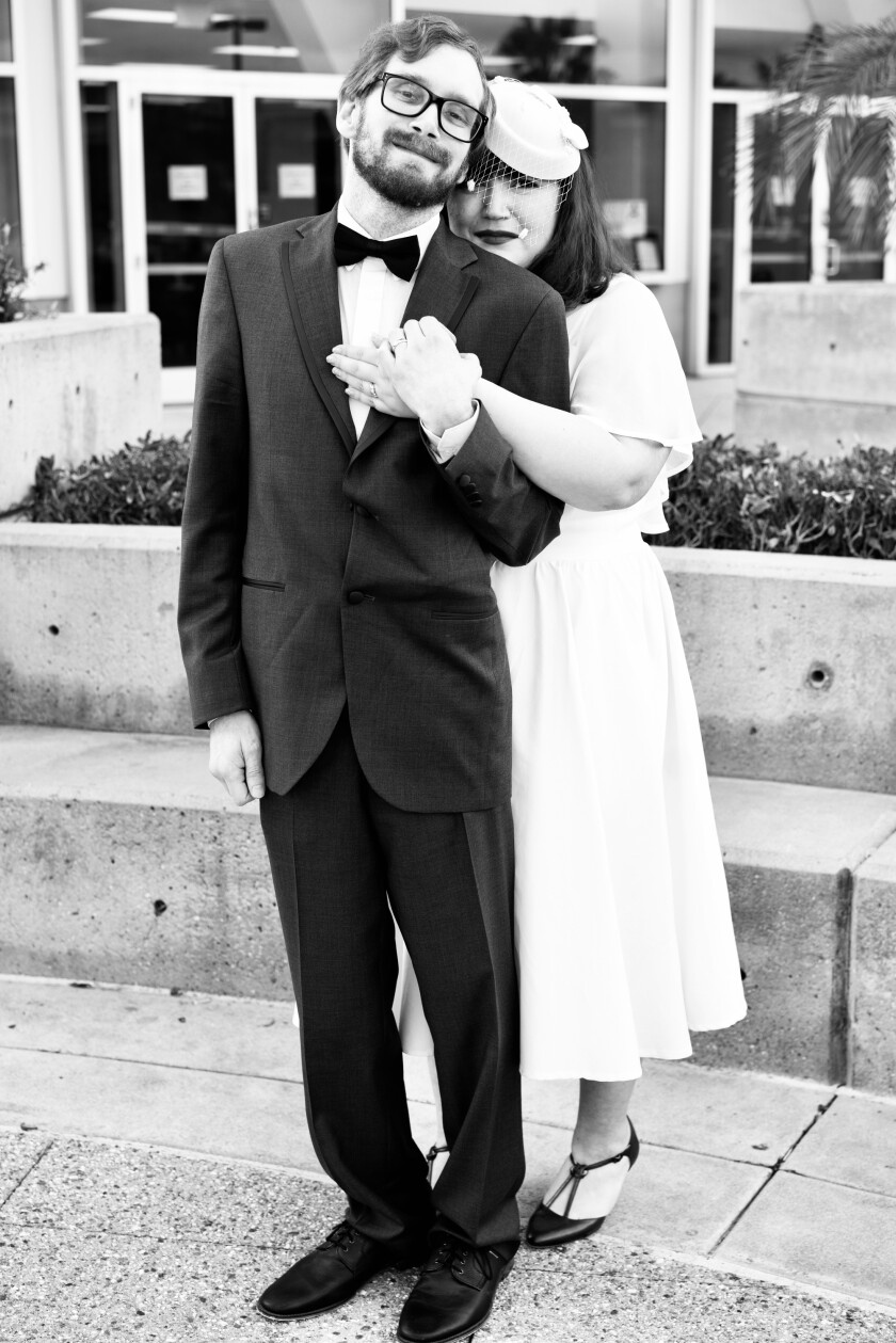 A man in a tux holds the hand of a woman in a white dress.