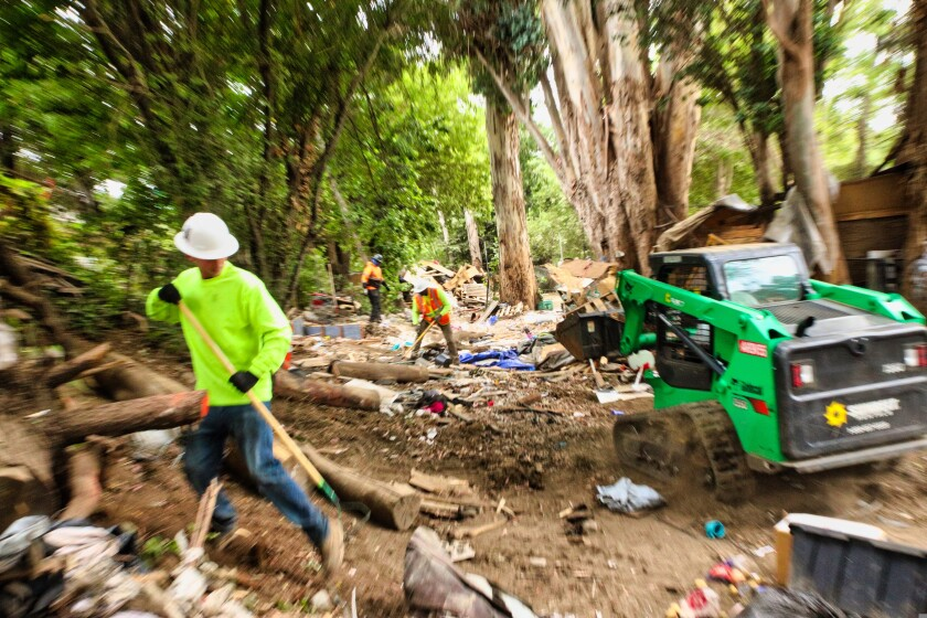 """Workers from contractor Dillard's Environmental Services clean up the """"Hell's Trail"""" encampment Monday."""
