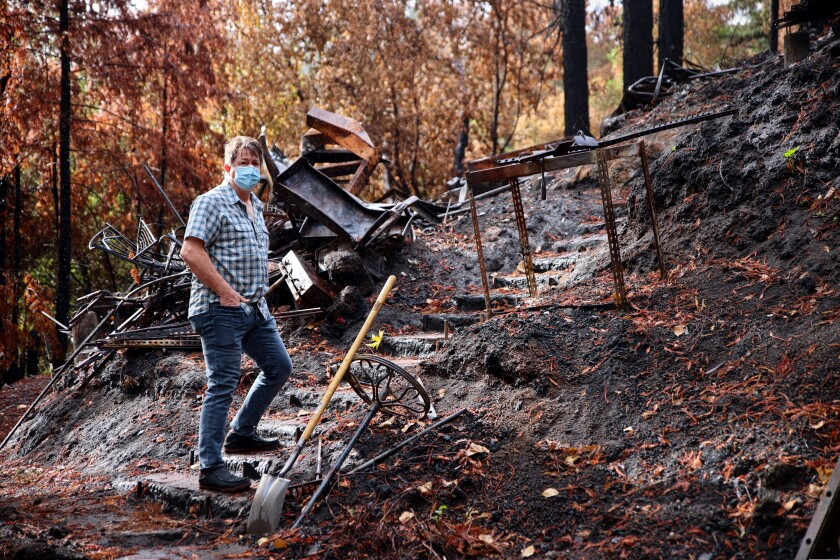 A man stands at the base of stairs on a steep slope in burned land.