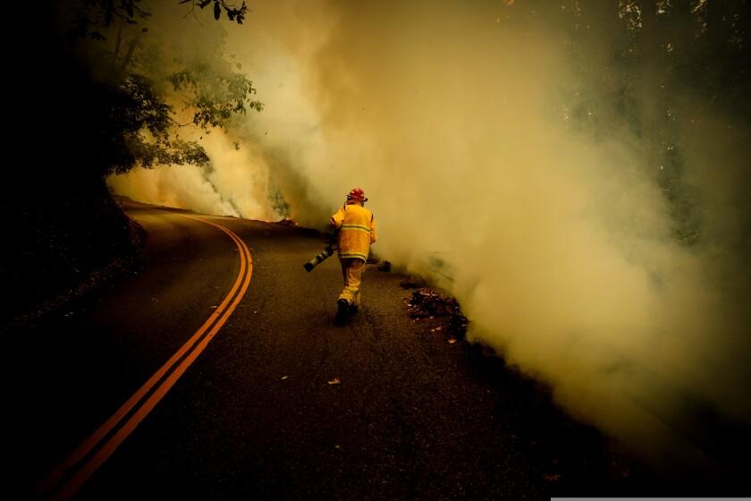 Santa Cruz Sentinel photographer Shmuel Thaler totes his camera during last year's CZU fires in the Santa Cruz Mountains.