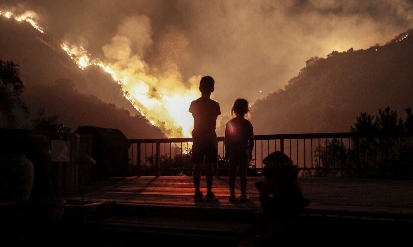 Iris, 4, and Castle Snider, 8, look on as the Bobcat fire burns the hillsides behind their Monrovia home in September.