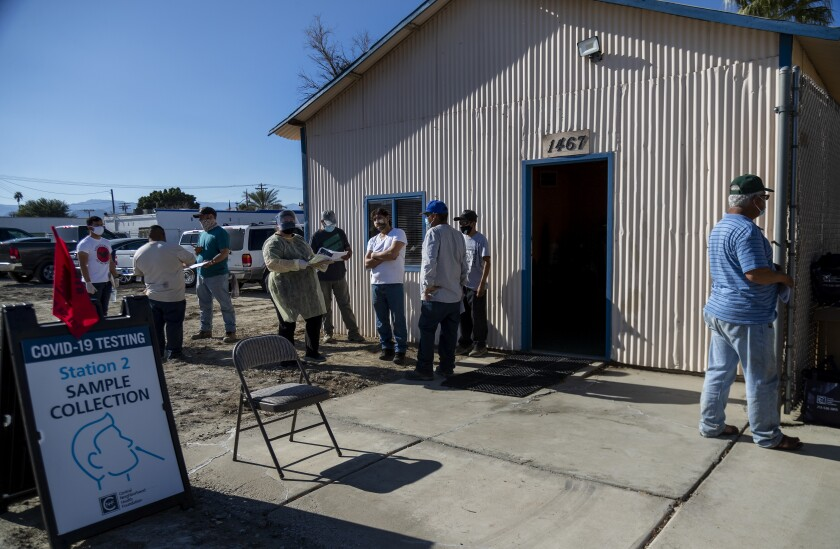 Farmworkers line up to receive the COVID-19 vaccine.