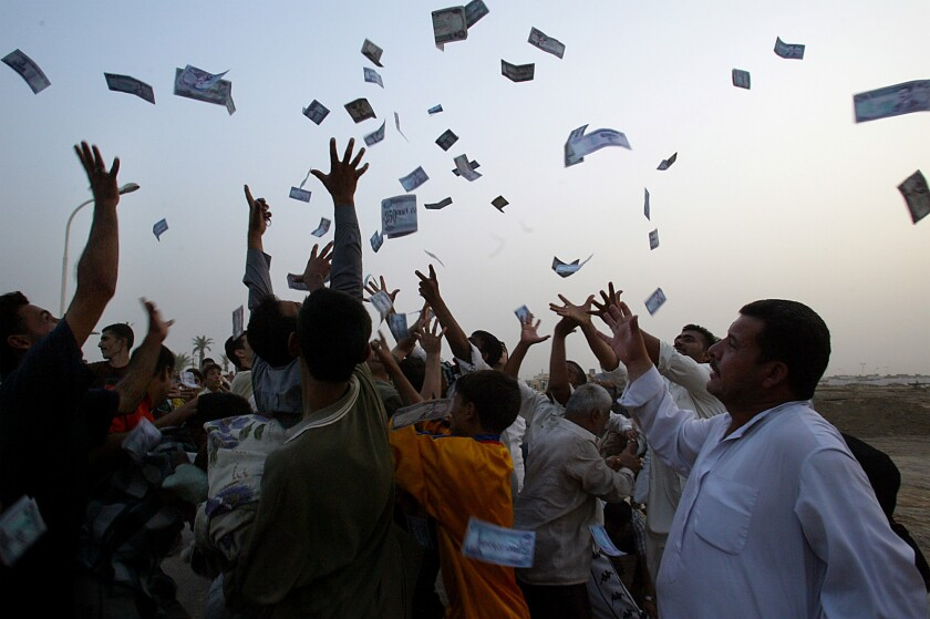 A group of people throw cash into the air