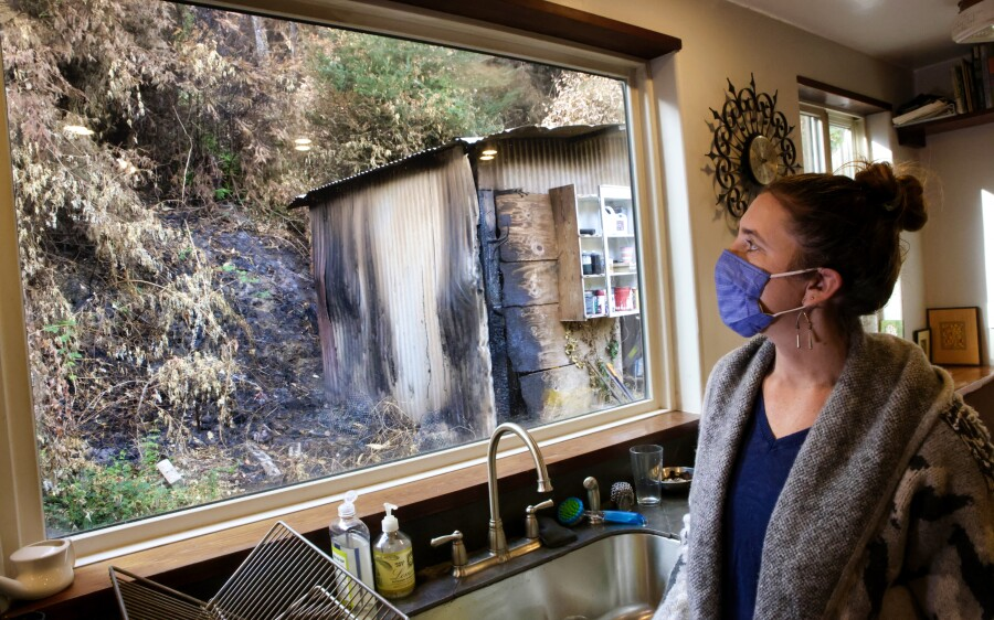 Amber Turpin looks out her kitchen window at her yard and shed that were charred in the CZU Lightning Complex fires.