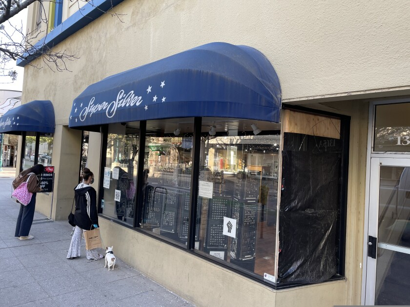 A boarded-up window at Super Silver Jewelry shows where the store was broken into early Wednesday.