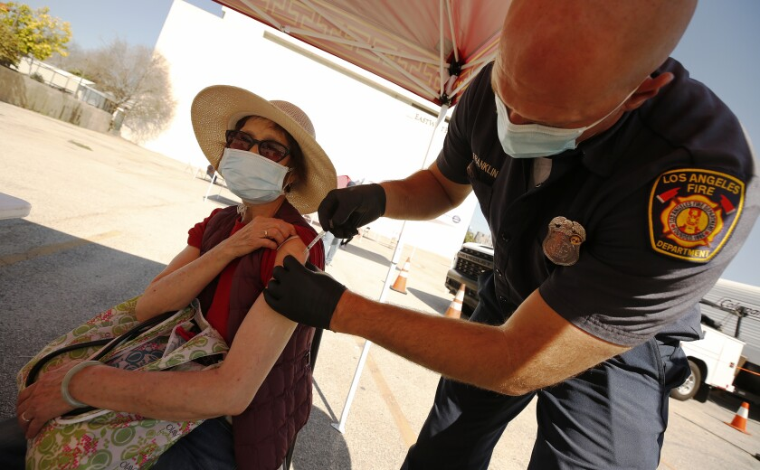 LOS ANGELES, CA - FEBRUARY 24: Yuyao Lui, 76, receives the Pfizer COVID-19 vaccine from LA City Firefighter Paramedic Joseph Franklin as the LA City CORE mobile team is staging a COVID-19 vaccination clinic in Chinatown for senior citizens, in an attempt to improve access to the vaccine among vulnerable populations. Chinatown on Wednesday, Feb. 24, 2021 in Los Angeles, CA. (Al Seib / Los Angeles Times).