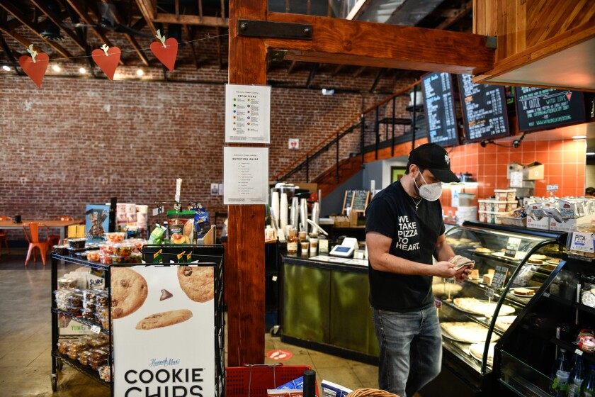 Andrew McDowell, owner of With Love Market & Cafe, rearranges the pastry case at his cafe