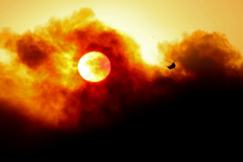 GOLETA, CALIF. - OCT.13, 2021. The sun is partially obscured by smoke as a firefighting helicopter prepares to make a water drop on the Alisal fire near Goleta on Wednesday, Oct. 13, 2021. (Luis Sinco / Los Angeles Times)
