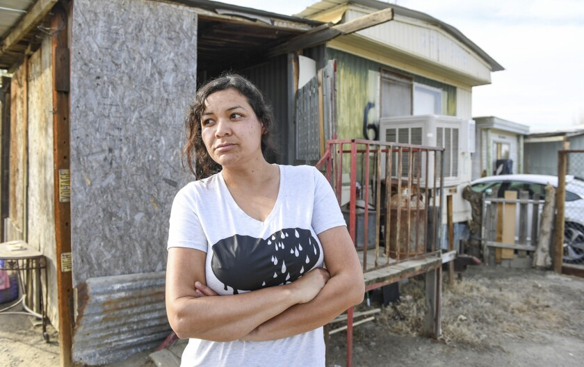 Carolina Navarro, 34, stands outside the mobile home she has been renting for the past 12 years, in Cantua Creek on Tuesday, March 2, 2021. Navarro is divorced with two children and has been out of work since November. Photo by Craig Kohruss/The Fresno Bee