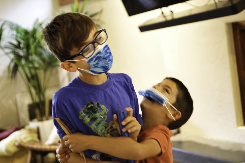 Cooper Sanyal, 8, plays with his brother Gavin, 5, before heading off to school in Santa Cruz.
