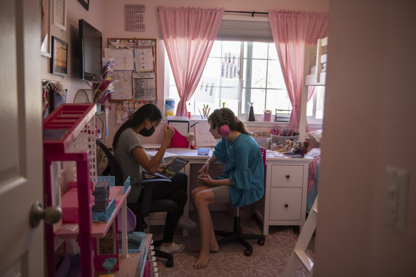 Ellie sits in her room with a behavioral therapist during class time in Monrovia, on Sept. 15, 2021.