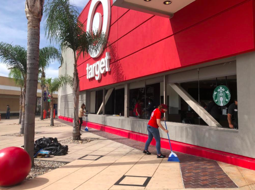 Workers clean up broken glass on Sunday at the Target store at Grossmont Center in La Mesa.