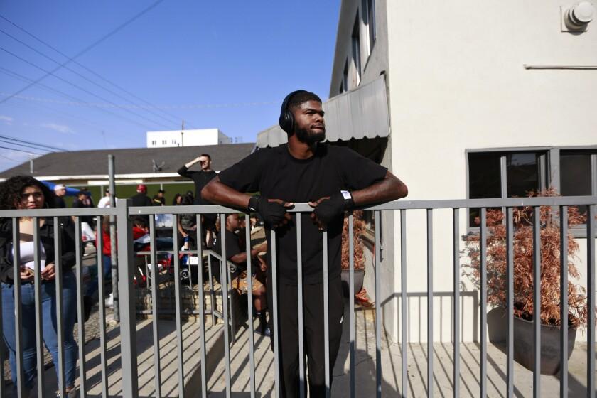 Albert Marion, wearing headphones, stands at an iron railing.