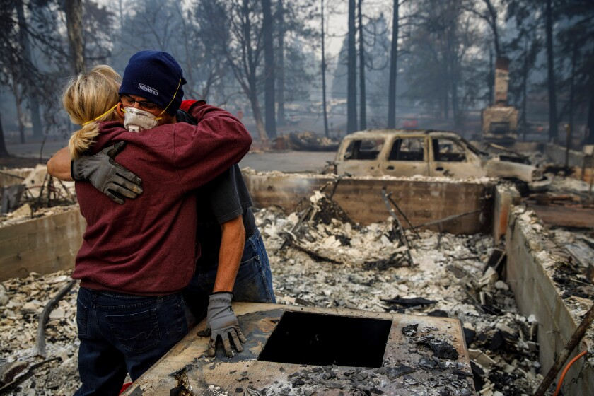 Michael John Ramirez hugs his wife, Charlie, as they search the rubble of their destroyed home in Paradise, Calif.