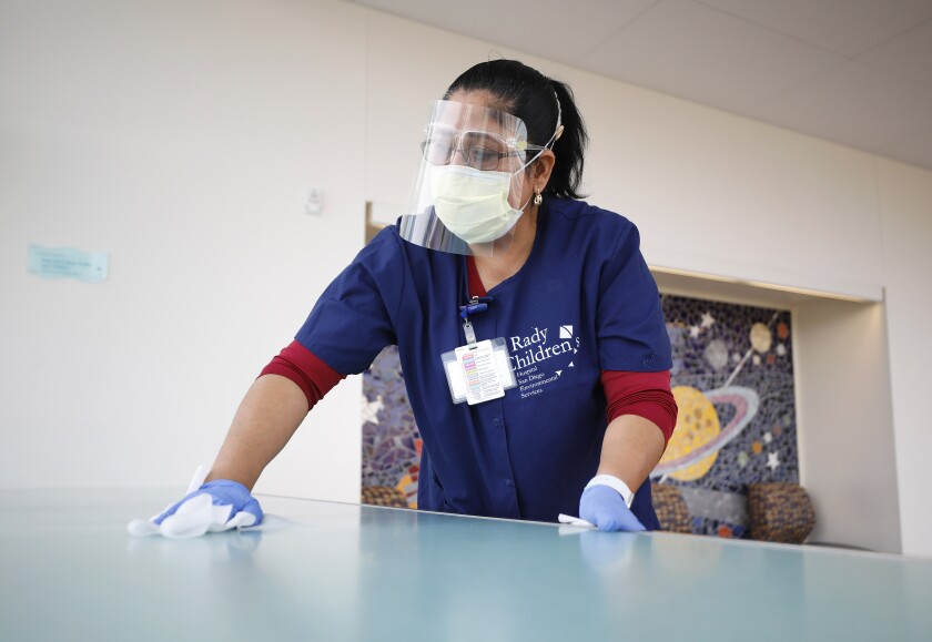 A woman in blue scrubs and a face shield cleans a hospital room