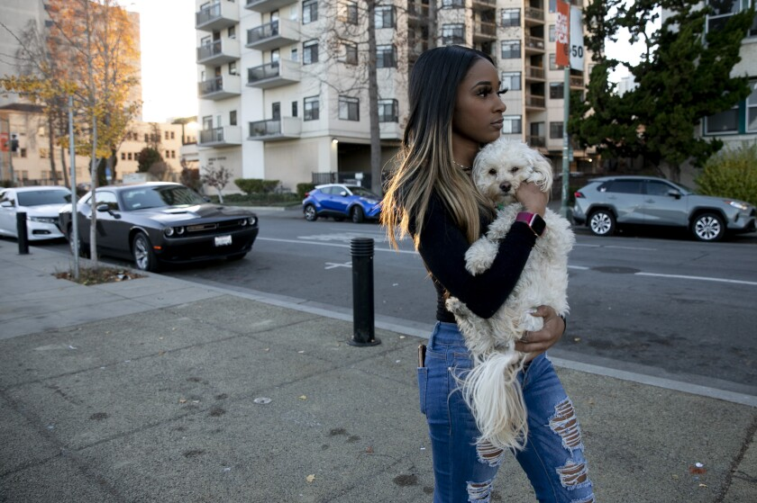 Jhonae Mazique carries her dog, Simba, to her friend's apartment near Lake Merritt where she's currently staying