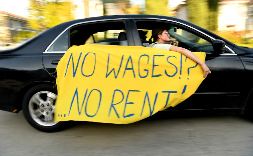 """A car moves down a street with a sign reading, """"No wages!! No Rent!"""""""