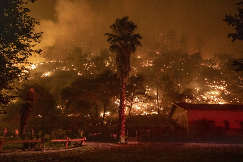 The LNU Lightning Complex wildfire burns behind the Canyon Creek Resort in Winters on Aug. 20, 2020.