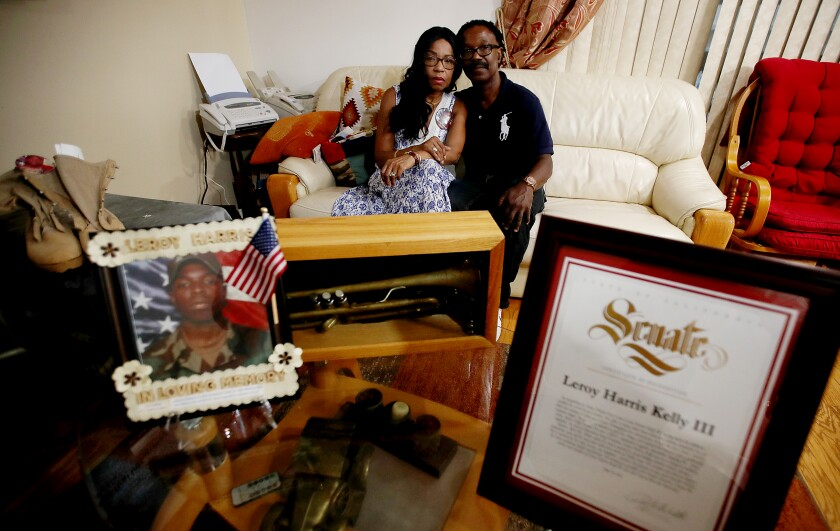 Guiselle and Leroy Harris Jr. sit with mementos of their son, including his combat boots, citations and pictures.