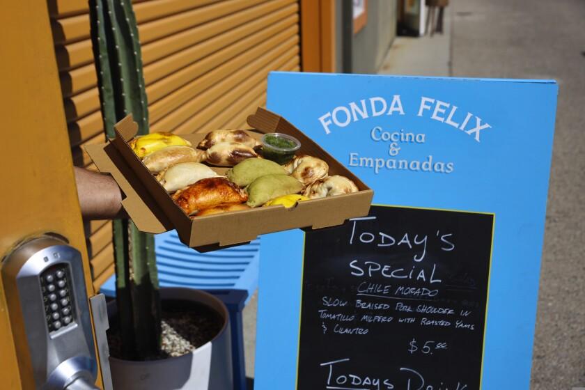 A hand sticks out with a tray of empanadas from Fonda Felix's Westside Santa Cruz location
