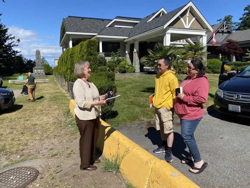 Notary public Julia Carlson, left, stands in Point Roberts, Wash., talking to Khue Le and his wife, Shelby, in Canada.