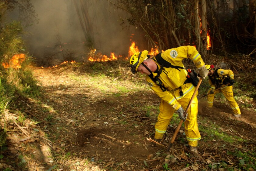 Firefighters from Aptos work to extinguish a blaze off of Gillette Road near Watsonville in January.
