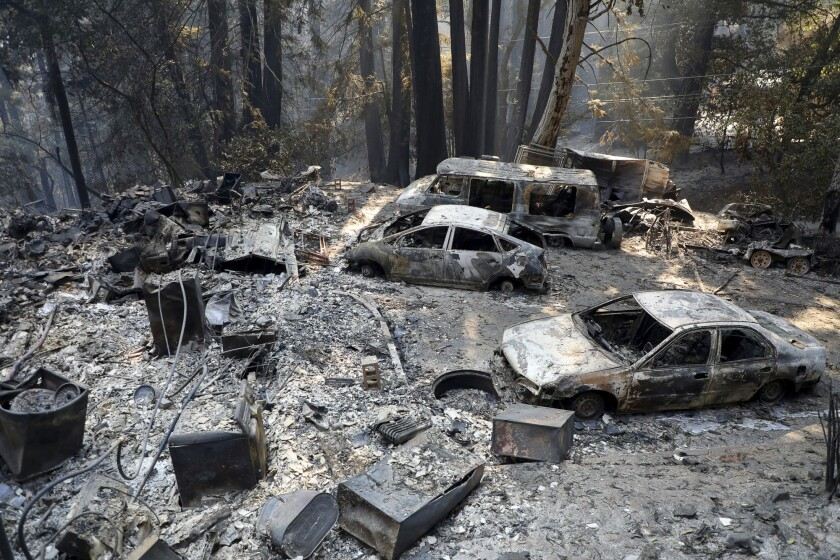 Burned cars are photographed at a home during the CZU Lightning Complex Fire