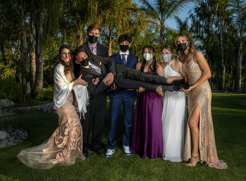 Students in prom attire pose for a photo holding one of their friends and wearing masks