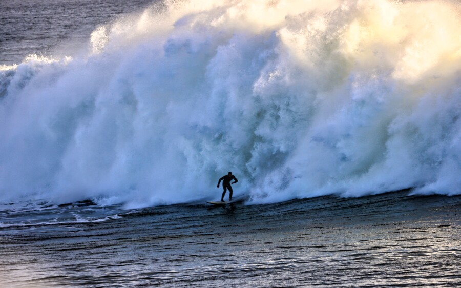 A surfer takes on a massive wall of whitewater on Dec. 8, 2020.