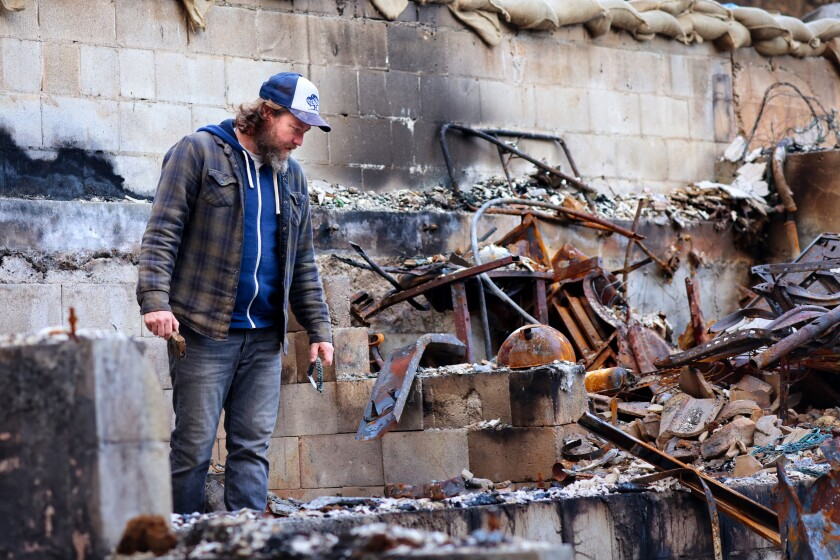 Jon Payne surveys the charred remains outside his Boulder Creek home.