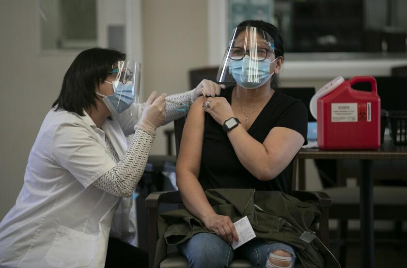 Personal care assistant Riza Green receives a COVID-19 vaccine