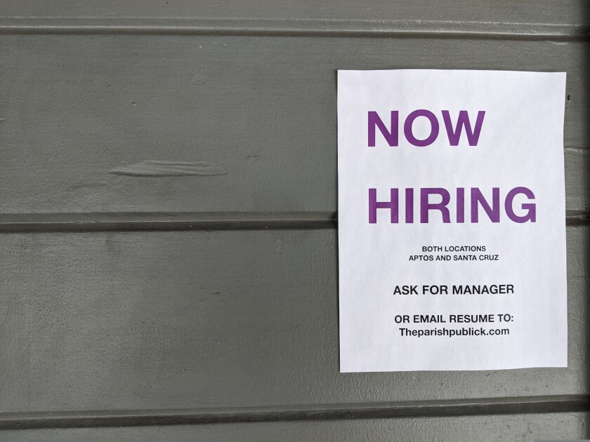 A now hiring sign hangs outside the entrance of Parish Publick House in Aptos on Tuesday.