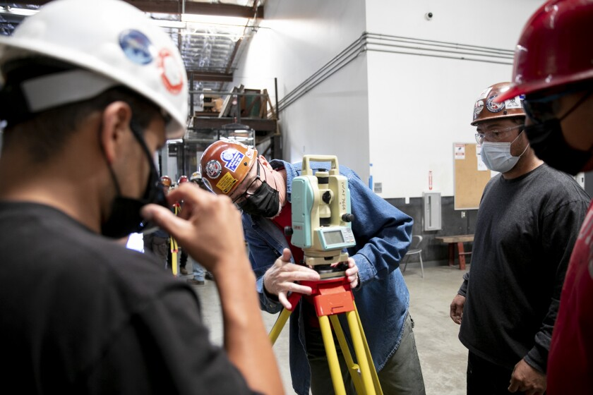 Apprenticeship instructor Mike Miller, center, demonstrates how to set up a theodolite