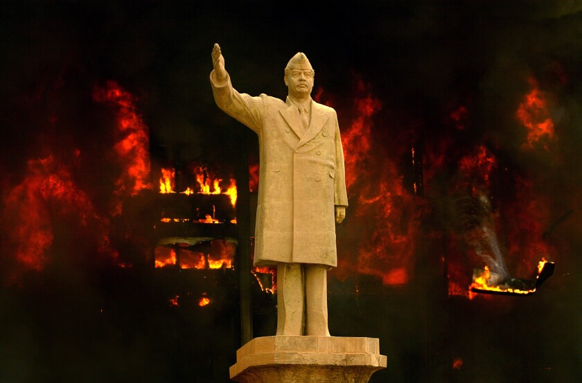 A statue of Saddam Hussein with his arm raised in front of a burning building
