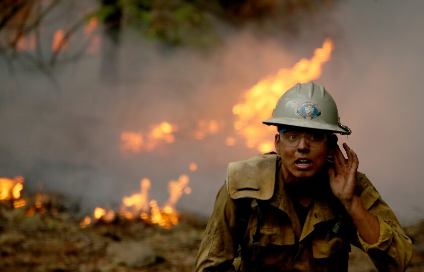 A firefighter battles the Dixie Fire in the mountainous and forested terrain near Janesville