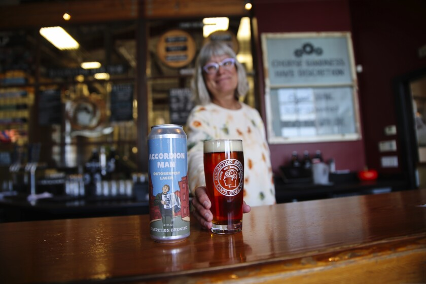 Kathleen Genco, the owner of Discretion Brewing, with a can of her Accordion Man Oktoberfest Lager.