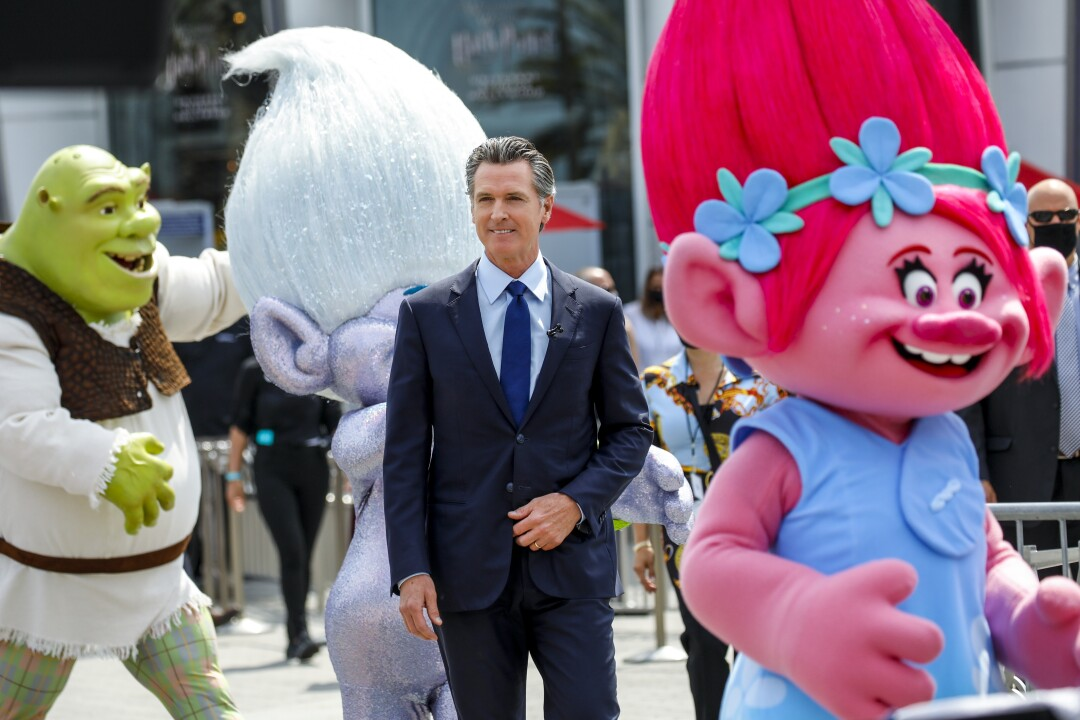 Gov. Gavin Newsom alongside Shrek and Troll-doll characters