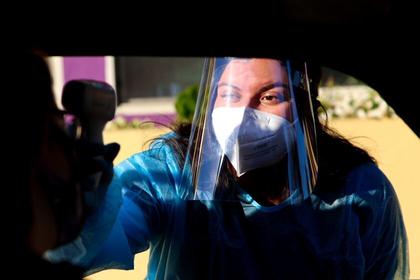 A healthcare worker in PPE takes the temperature of a person at a drive-thru COVID-19 testing facility on Dec. 10, 2020.