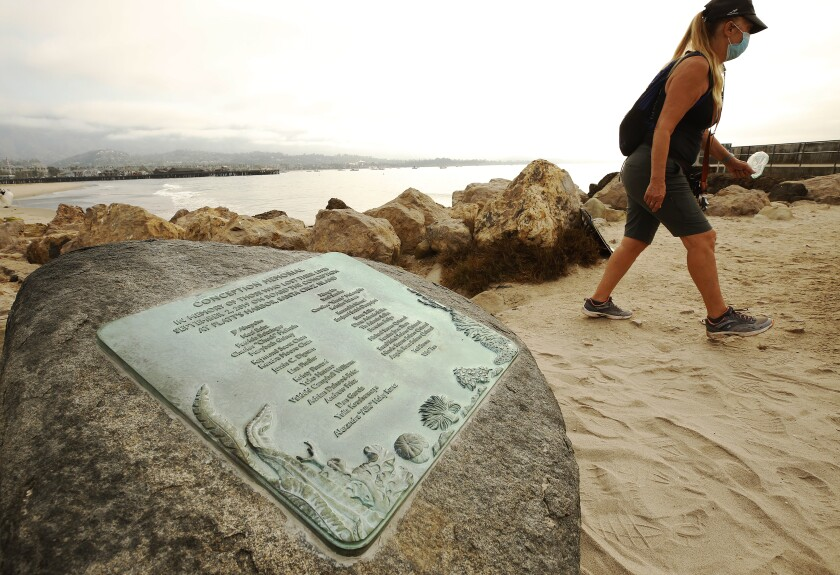 A woman walks past a Santa Barbara memorial for the 34 people who died in the Conception boat fire