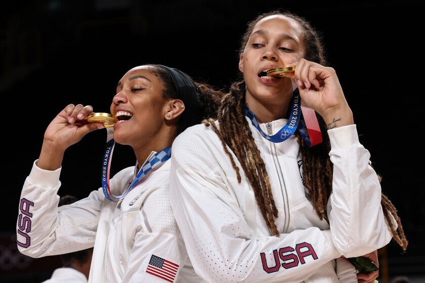 U.S. women's basketball players A'Ja Wilson and Brittney Griner bite their gold medals.