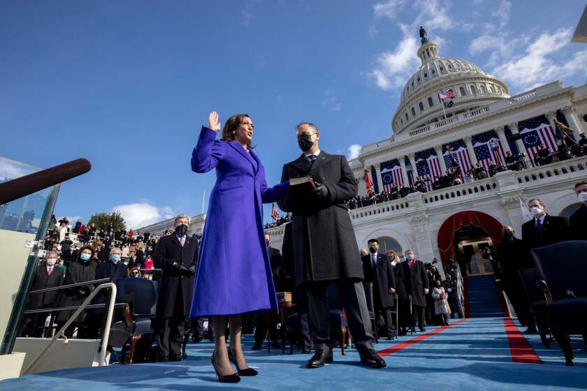 Vice President Kamala Harris taking oath of office with her hand on a bible held by husband, Second Gentleman Doug Emhoff